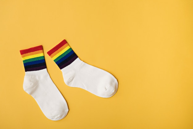 Witte sokken met regenboogstrepen op gele achtergrond, lgbt-cadeau-idee, lgbtq-cadeau, kopieer ruimte