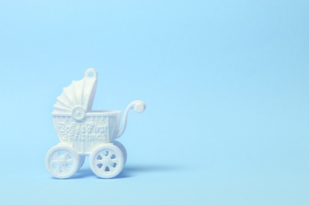 Witte speelgoed kinderwagen op blauwe achtergrond. kopie ruimte.
