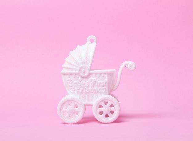 Witte speelgoed kinderwagen op roze achtergrond. kopie ruimte.