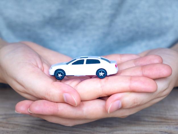 Witte speelgoedauto in de handen van vrouwen