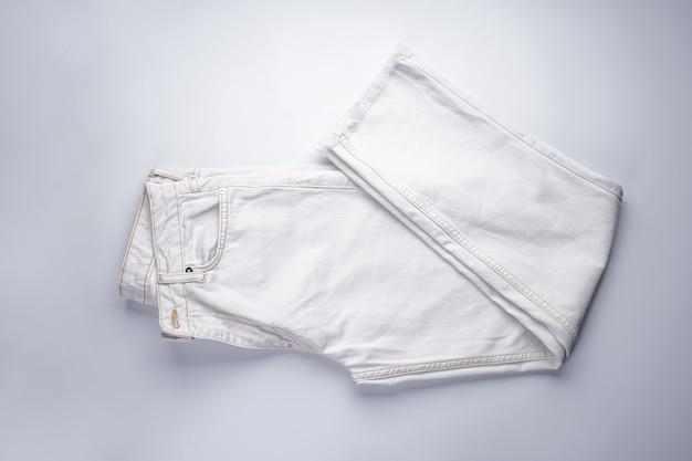 Witte spijkerbroek gestapeld, bovenaanzicht.