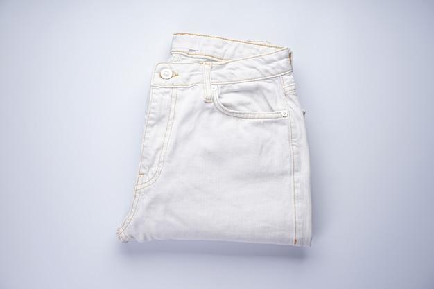 Witte spijkerbroeken zijn gestapeld. plat leggen.