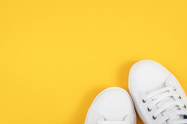 Witte sportschoenen, sneakers met schoenveters op een gele achtergrond. sport levensstijl concept bovenaanzicht plat lag