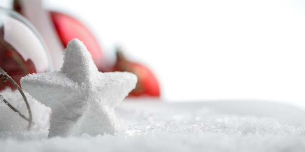 Witte ster met rode kerstversiering in sneeuw