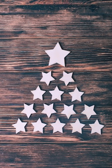 Witte sterren in de vorm van een kerstboom op een houten ondergrond