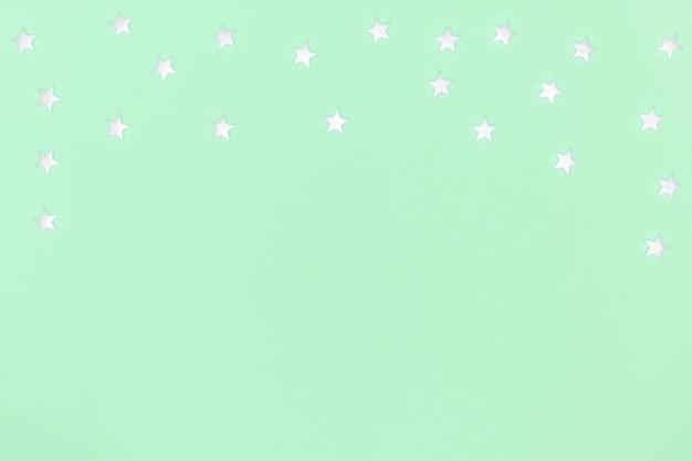 Witte sterren op pastelgroen oppervlak