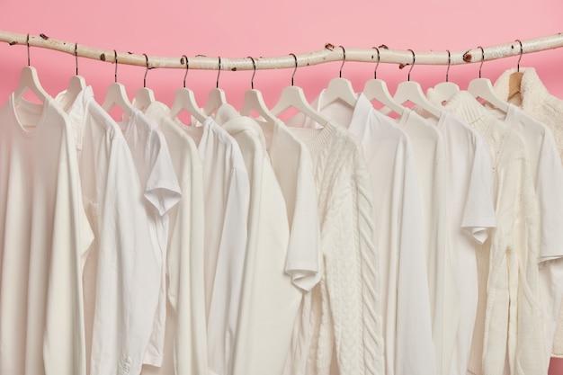 Witte stevige kleren die in één rij op houten rekken hangen tegen roze achtergrond. grote keuze voor vrouwen in winkel.