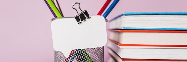 Witte sticker, boeken, blocnote en pen op de werkplek