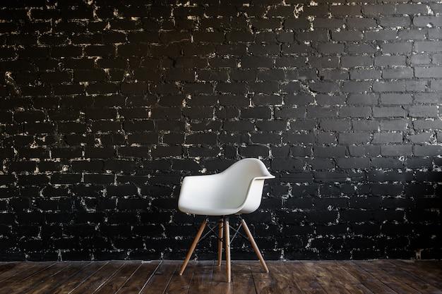 Witte stoel die zich in ruimte op bruine houten vloer over zwarte bakstenen muur bevindt