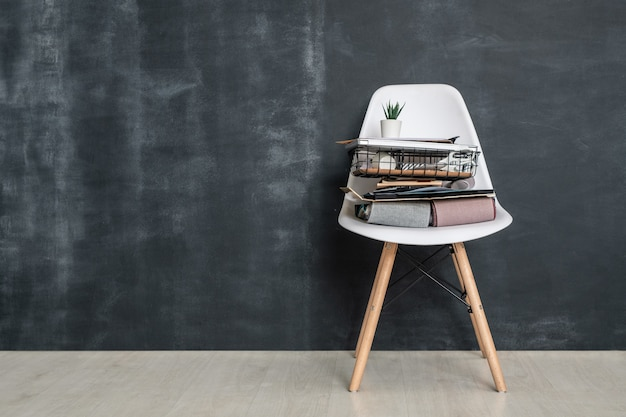 Witte stoel met gevouwen textielmonsters, mand met kantoorbenodigdheden, album met foto's van huisinterieur en kamerplant per bord