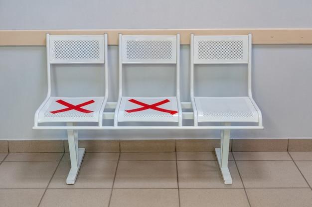 Witte stoelen met de rode kruisen tijdens de covid-19 pandemie