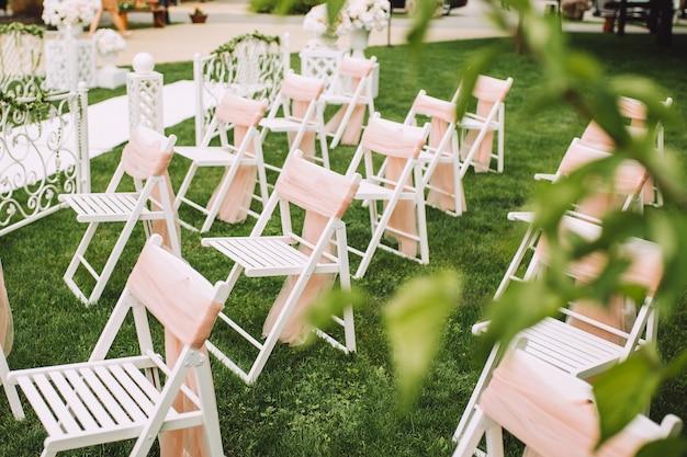 Witte stoelen versierd met roze linten, staan in de zone van de huwelijksceremonie in een bos