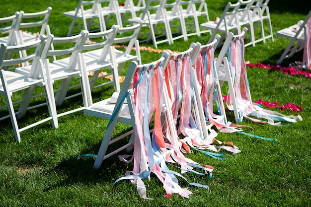 Witte stoelen voor een huwelijksceremonie op een groene weide met kleurrijke strepen