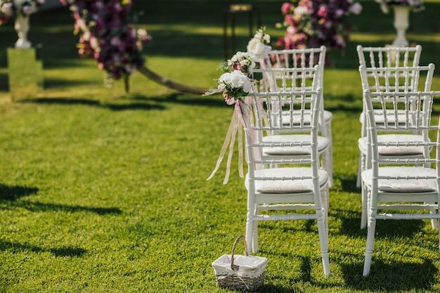 Witte stoelen voor gasten versierd met bloemen