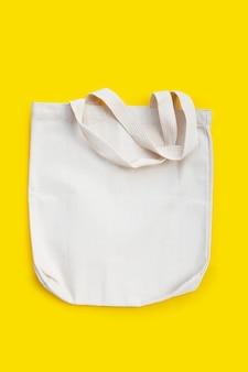 Witte stoffen tas op geel oppervlak