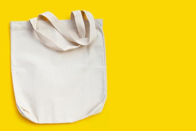 Witte stoffen tas op gele achtergrond.