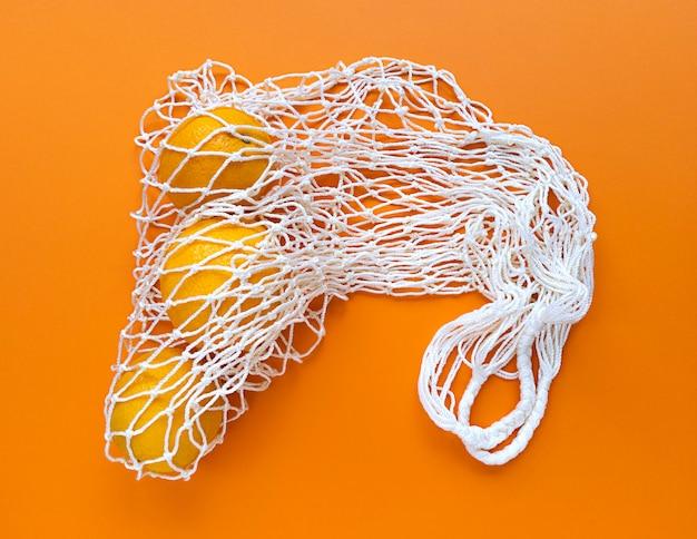 Witte string katoenen eco tas met sinaasappels op oranje achtergrond. monochroom eenvoudig plat. ecologie nul afval concept.