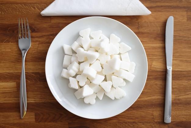 Witte suiker ligt op bord naast vork en mes