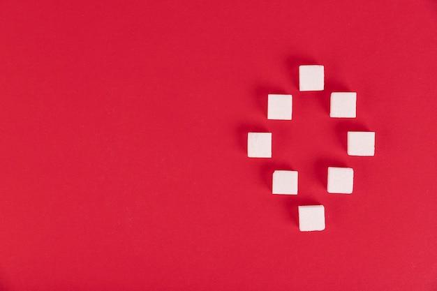 Witte suikerklontjes op een rode achtergrond in de vorm van het getal nul. kopieer de ruimte.