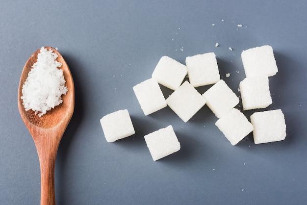 Witte suikerkubus zoet voedselingrediënt en suiker in lepel