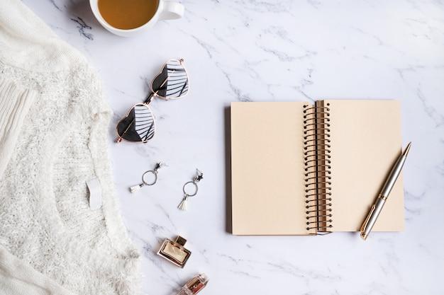 Witte sweater, vrouwentoebehoren, koffie, notitieboekje, slimme telefoon op marmeren hoogste mening als achtergrond. vrouwenkleding. plat leggen, kopie ruimte