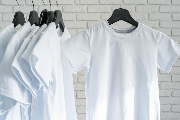 Witte t-shirt opknoping op hanger tegen bakstenen muur, kopieer ruimte