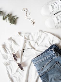 Witte t-shirtjeans, zonnebril, halsband en witte tennisschoenen op witte achtergrond.