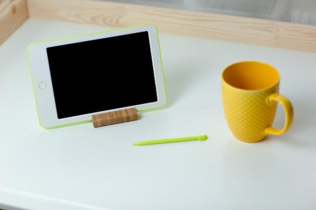 Witte tablet en gele kopje thee op witte tafel. thuiskantoor terwijl u zelf isoleert, thuiswerkend. online onderwijs, e-learning tijdens quarantaine.