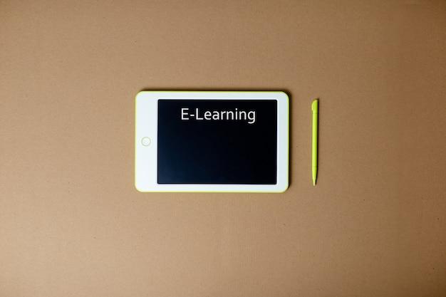 Witte tablet en pen op ambachtelijke papier achtergrond. thuiskantoor terwijl u zelf isoleert, thuiswerkend. online onderwijs, e-learning tijdens quarantaine.
