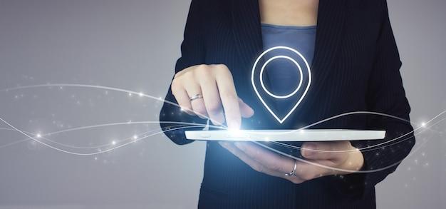 Witte tablet in zakenvrouw hand met digitale hologram locatie marker teken op grijze achtergrond. pin adres locatie concept.
