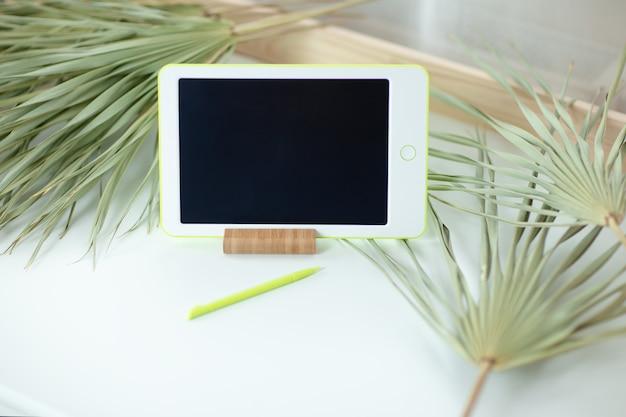 Witte tablet met pen op witte lijst met droge rond palmbladen. thuiskantoor terwijl u zelf isoleert, thuiswerkend. online onderwijs, e-learning tijdens quarantaine.