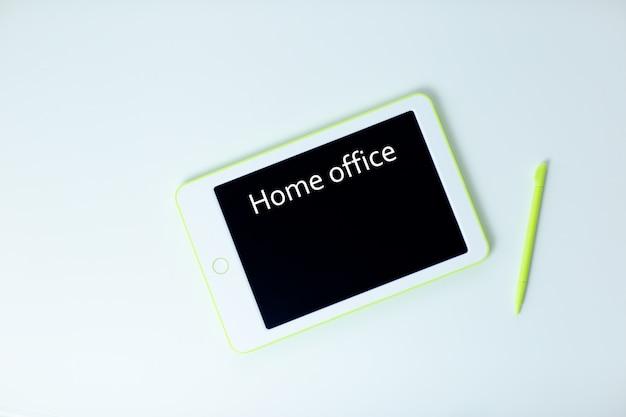 Witte tablet met pen op witte tafel. thuiskantoor terwijl u zelf isoleert, thuiswerkend. online onderwijs, e-learning tijdens quarantaine.