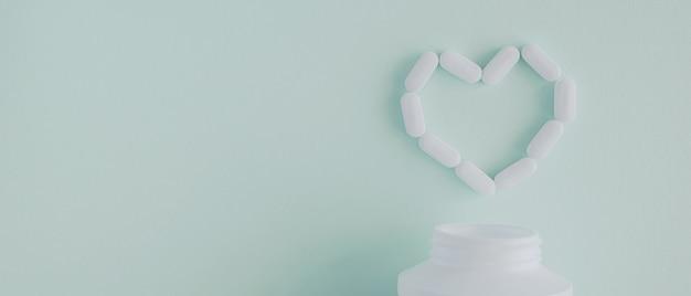 Witte tabletten en pillen in hartvorm en fles