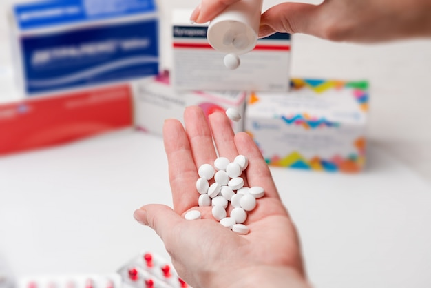 Witte tabletten in de hand van de vrouw