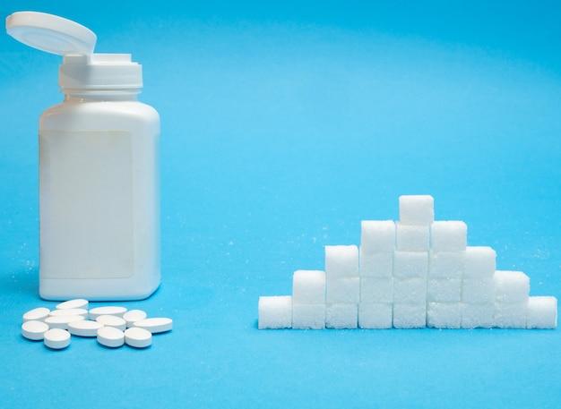 Witte tabletten pillen van suikerzoetstof met grote fles blanco etiket versus stapel geraffineerde normale suiker