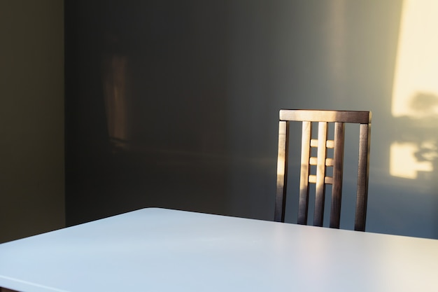 Witte tafel en houten stoel op grijze achtergrondmuur in zonlicht