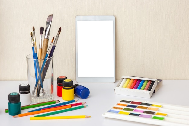 Witte tafel met digitale tablet op witte tafel met kleurrijke tekenbenodigdheden. kwasten, aquarellen, kleurpotloden, potlood, acrylverf. het concept van tekencursussen. bespotten