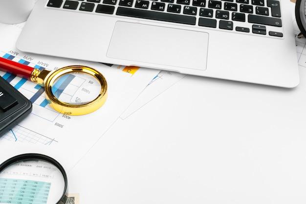 Witte tafel met een computer, een grafiek, een vergrootglas