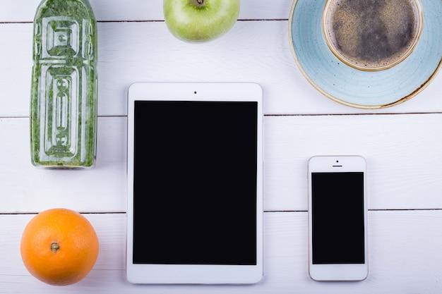 Witte tafel met een tablet, telefoon, detox en groene appel. bovenaanzicht hoek met kopie ruimte