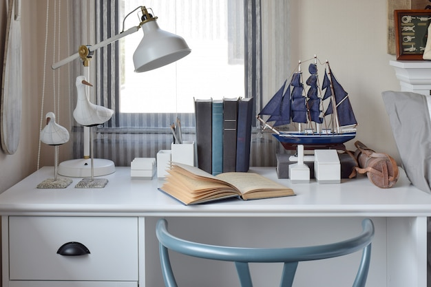 Witte tafel met houten stoel boeken en lamp i