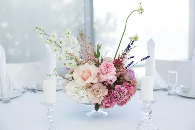 Witte tafel voor evenementen geserveerd en gedecoreerd met delicate verse bloemen