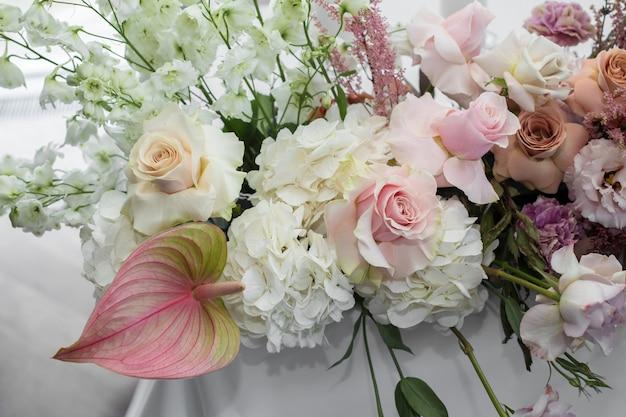 Witte tafel voor evenementen, geserveerd en gedecoreerd met delicate verse bloemen