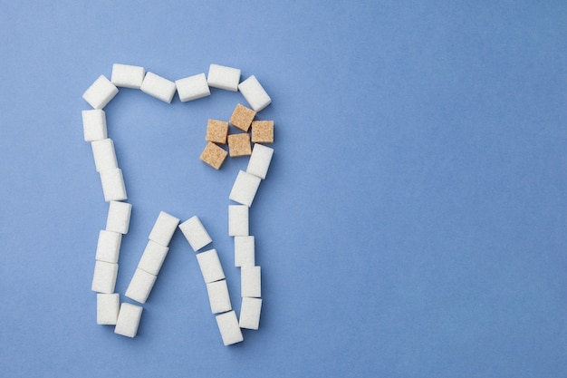 Witte tand met bederf van suiker op blauw
