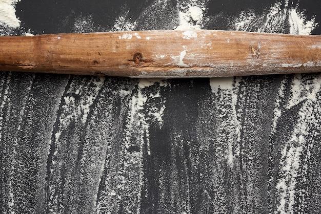 Witte tarwemeel verspreid over een zwarte tafel en zeer oude bruine houten deegroller