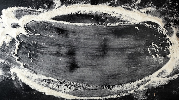 Witte tarwemeel verspreid over een zwarte tafel