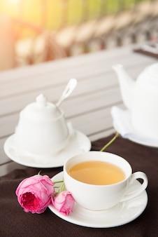 Witte thee beker met theepot en suikerpot op tafel