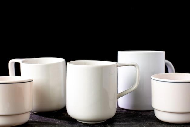Witte thee en koffiemokken van verschillende vormen op een houten tafel