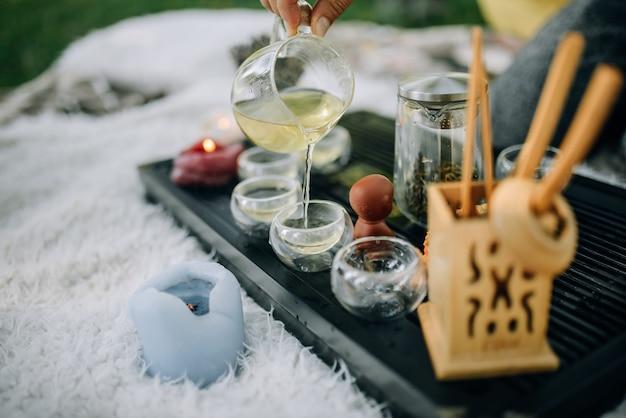 Witte thee wordt van dichtbij in glazen bekers gegoten theeceremonie in het park