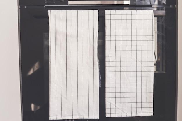 Witte theedoek hangt aan het handvat van de oven, productmodel