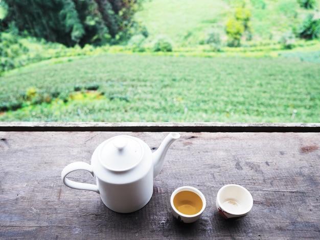 Witte theepot en kopjes op vintage houten tafel over groene thee boerderij.